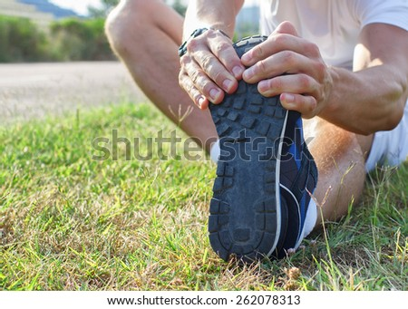 Wide view of a sports man body figure stretching on a track - stock photo