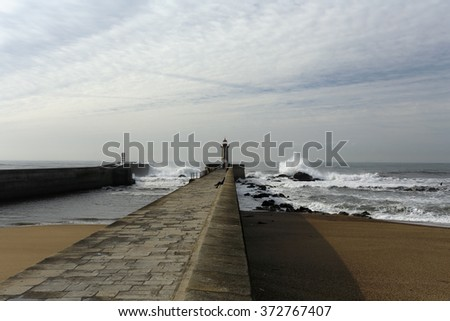Wide view of Douro river mouth south piers, the old and the new one, in a beautiful but stormy day during low tide - stock photo