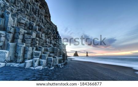 Wide view of Reynisdrangar rock formations on Reynisfjara Beach at sunrise, Halsanefhellir, Iceland. - stock photo