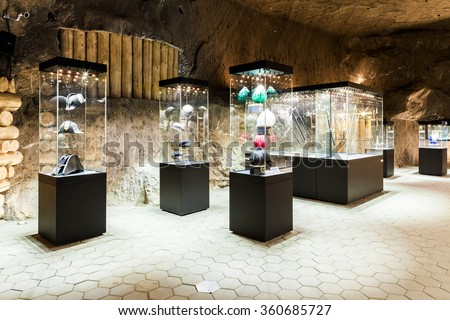 Wieliczka - Poland - April 23, 2015: One of the chambers of Salt Mine Museum Exhibition. In glass-case are shown hats, caps, helmets and other miners accesories.  - stock photo