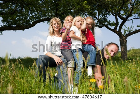 Wife and daughters horse riding daddy - all of them looking happy, the father only a bit - stock photo
