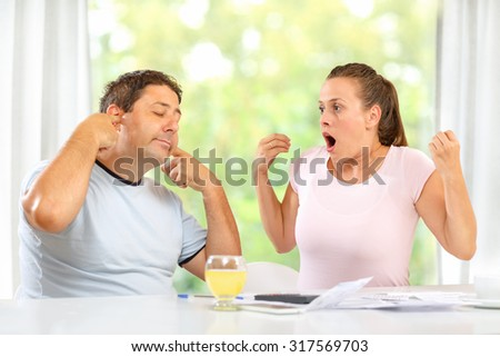 Wife and husband arguing over large bills. Man isn't listening - stock photo