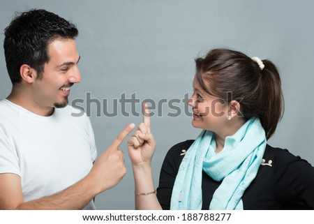 Wife and husband talking each other with finger gestures - stock photo