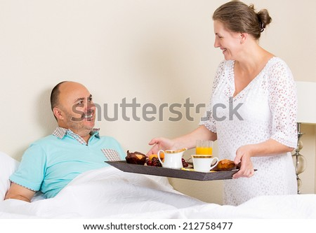Wife bringing breakfast in bed to delighted husband in bedroom at home. Positive emotions, face expressions, feelings. Happy family life, strong relationship concept. - stock photo