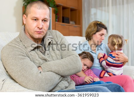 Wife can't forgive his husband. Man is sitting on a sofa on the front and his family is sitting behind him. Two crying daughters and a dissapointed wife - stock photo