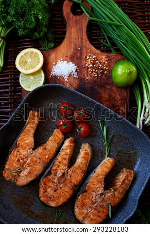 Wife waits for guests to cook for dinner salmon steaks,Fish steaks are on the grill pan with rosemary and tomatoes,On a wooden board with a pan put the fried fish - stock photo