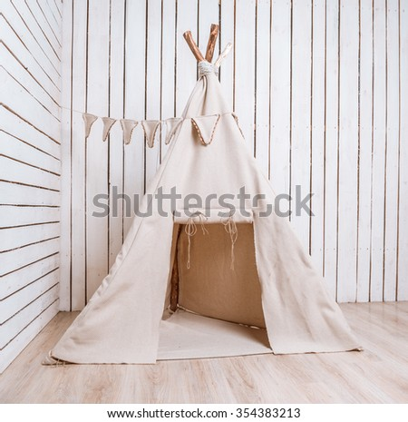 wigwam for children in a room with wooden planked walls - stock photo
