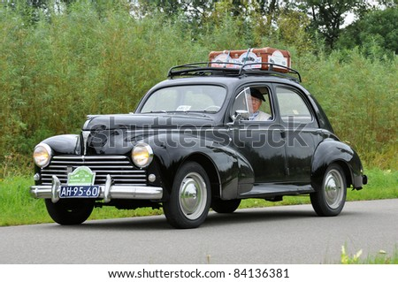 WIJHE, THE NETHERLANDS - SEPTEMBER 4: A Peugeot 203C from 1957 drives past at the 10th Diekdaegen classic car tour on September 4, 2011 in Wijhe, The Netherlands - stock photo