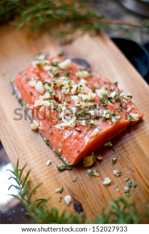 Wild Alaskan salmon fillet on a cedar plank that is ready to be grilled.  It's seasoned with garlic, rosemary, salt and pepper. - stock photo