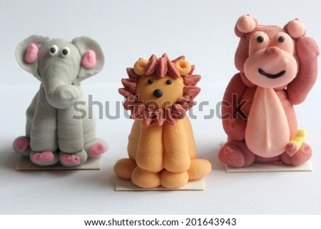 wild animals lion elephant bear cute colorful cake toppings art. interesting and unique artwork of wildlife creatures created in a funny way for kids and children cakes and chocolate - stock photo
