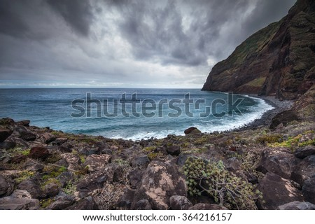 Wild bay on the Madeira island, dark clouds and turquoise sea - stock photo