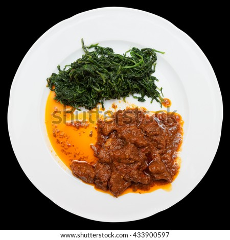 Wild boar stew with hot sauce and spinach isolated on black - stock photo