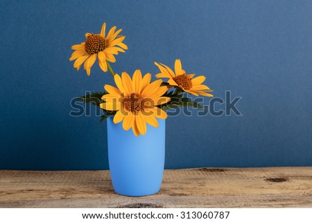 Wild flowers in a vase on a wooden table - stock photo
