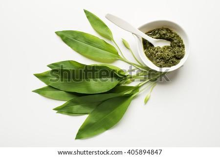 Wild garlic leafs and pesto on white background overhead shoot - stock photo