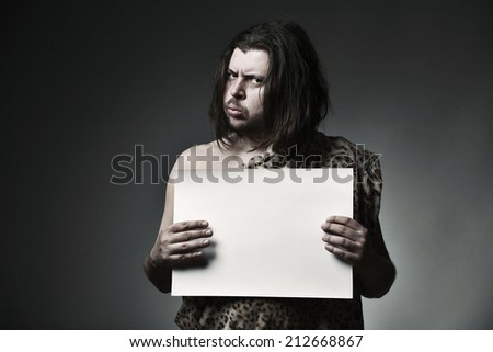 Wild man neanderthal in leopard skin hold empty paper sheet. - stock photo