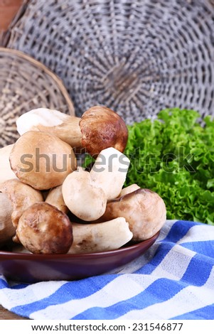 Wild mushrooms on plate with herbs and greens on table - stock photo