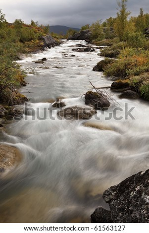 Wild river in Lapland on a cloudy day - stock photo