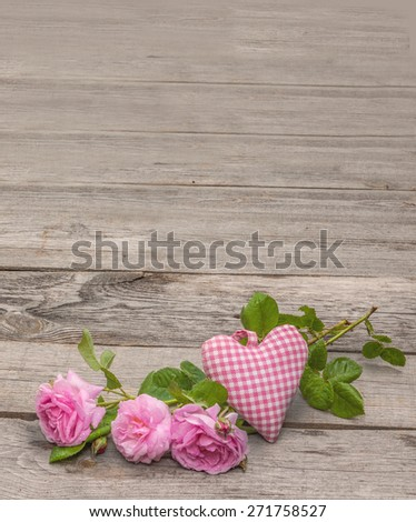 Wild rose and heart on old wooden background - stock photo