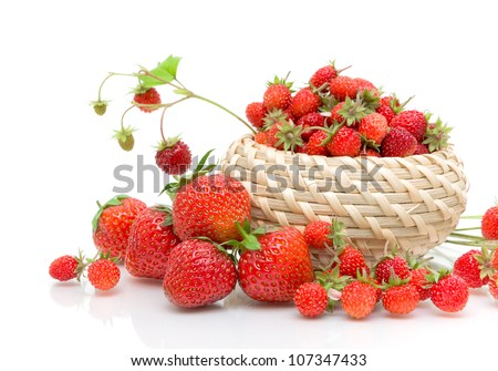 Wild strawberries in a wicker basket and strawberries closeup on white background - stock photo