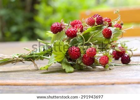 Wild strawberry bouquet on garden table - stock photo