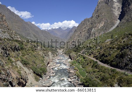Wild Urubamba river flowing through valley with high snow capped mountains and blue sky in the background - stock photo