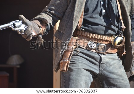 wild west cowboy with two guns and leather holsters - stock photo