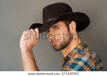 Wild West is his heart. Handsome young man adjusting his cowboy hat and looking at camera while standing against grey background  - stock photo