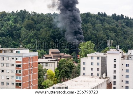 Wildfire burning near residential buildings producing a large column of smoke. - stock photo