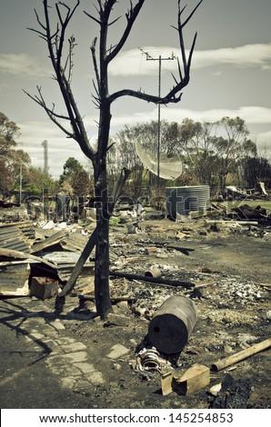 Wildfire devastation, Tasmania, Australia, 2012/2013. Remains of houses, with broken crockery, television aerial, satellite dish and burnt tree. - stock photo
