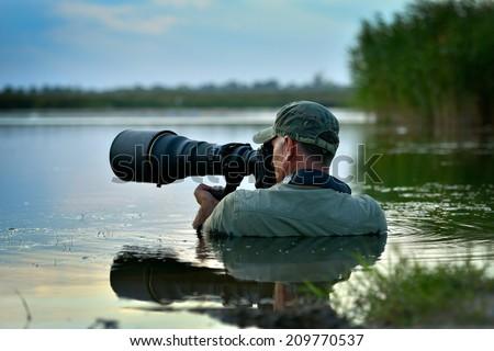 wildlife photographer outdoor, standing in the water - stock photo