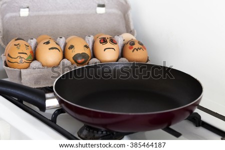 will we be the next? Eggs in a egg box are scared of to be chosen for omelet - stock photo