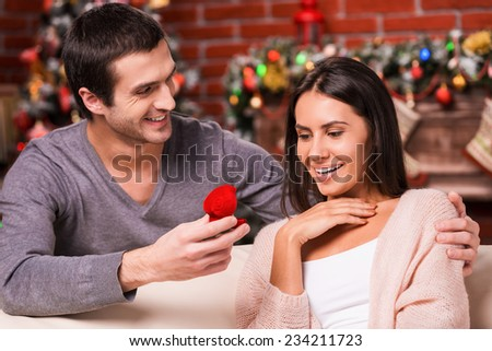 Will you marry me? Handsome young man making a proposal while giving an engagement ring to his girlfriend with Christmas Decoration in the background  - stock photo