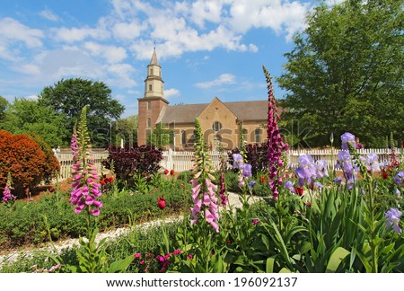 WILLIAMSBURG, VIRGINIA - APRIL 21 2012: Gardens of Colonial Williamsburg in front of Bruton Parish Church in spring. The restored town is a major attraction for tourists and meetings of world leaders. - stock photo