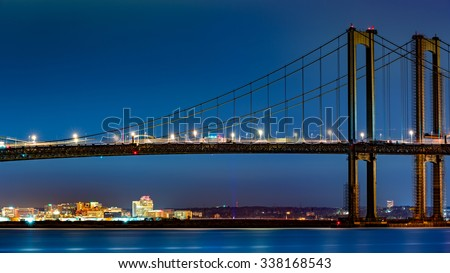 Wilmington skyline framed by Delaware Memorial Bridge, viewed from New Jersey, across the Delaware River. Wilmington is the largest city in the state of Delaware. - stock photo