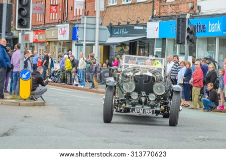 Wilmslow UK - July 9, 2013 : A vintage Bentley drives sideways during the annual public gathering of local sports and super cars in affluent Wilmslow, Cheshire - stock photo