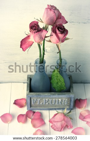 Wilted roses in rustic vase and fallen petals on wooden background. Vintage and film stylized image, grainy. Shallow DOF. - stock photo