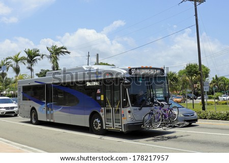 WILTON MANORS, FLORIDA - MAY 11, 2013: Blue and gray silver public transportation with two bicycles securely stored on the front of the bus as it travels through the sunny day city on Wilton Drive.  - stock photo