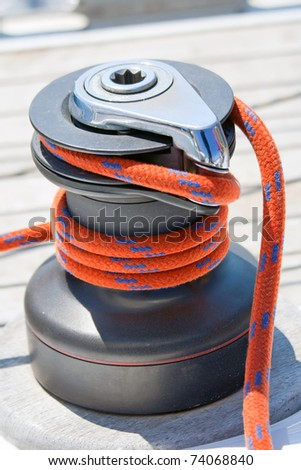 Winch with red rope on sailing boat - stock photo