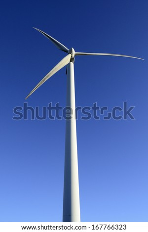 Wind energy business. Wind turbine closeup with blue sky background. Vertical view - stock photo