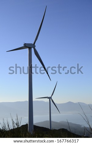 Wind energy business. Wind turbines silhouette and closeup with blue sky   - stock photo