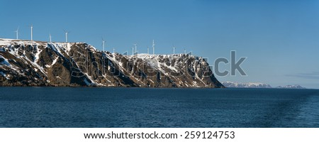 Wind Energy in Norway. The blue sea and gray cliff covered with snow on the background of a cloudless sky - stock photo