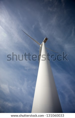 Wind energy turbine, isolated over a beautiful blue sky - stock photo