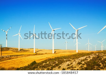 Wind farm at farmland in summer. Aragon, Spain - stock photo