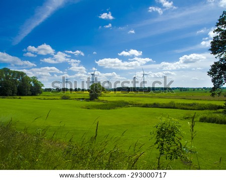 wind farm in agrarian landscape with meadows - stock photo