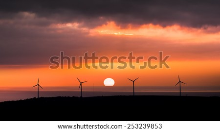 Wind Farm in front of setting sun - stock photo