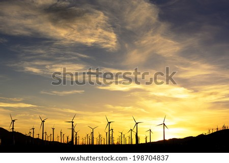 wind farm in silhouette at sunset - stock photo