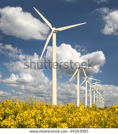 Wind farm with rapeseed field - stock photo