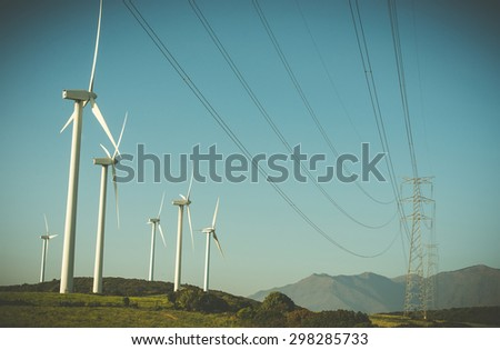 wind generator and high-voltage lines in a field on with blue sky and mountains on background - stock photo