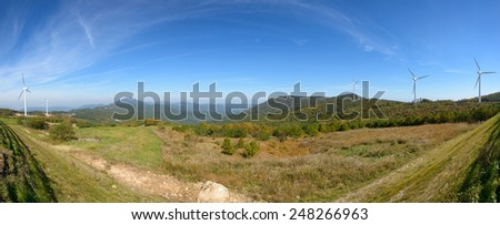 wind generator in a mountain with cloudy sky - stock photo
