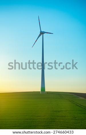 wind generator on the green field - stock photo